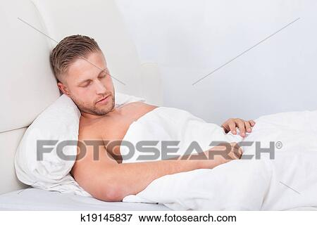 Picture Of Man Sleeping In Bed Propped Up Against The Pillows