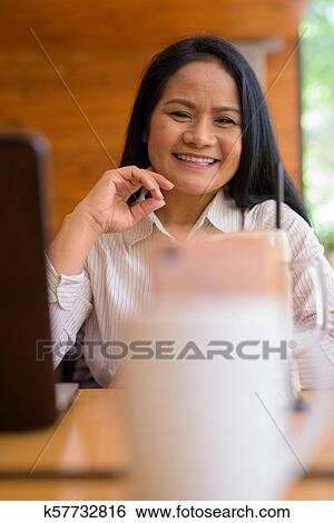Mature Asian Businesswoman Relaxing At Coffee Shop Stock Image