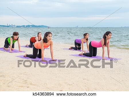 yoga class at sea beach in evening sunset group of people