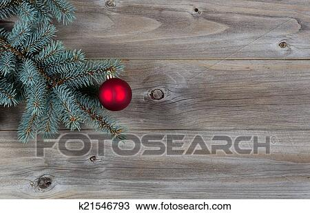 horizontal image of a single red christmas ornament hanging from a real blue spruce tree branch placed on rustic wooden boards