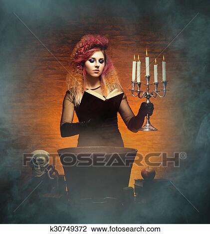 Beautiful Witch Casting A Spell Using A Magical Vat A Book And A Candlestick Halloween Concept Stock Image K30749372 Fotosearch