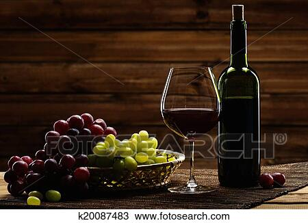 Stock Photo Of Bottle Of Red Wine Glass And Grape In Basket In