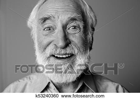6d0b30b89c72d Close up black-and-white portrait of aged happy pensioner with widely open  eyes while standing. Isolated on grey background