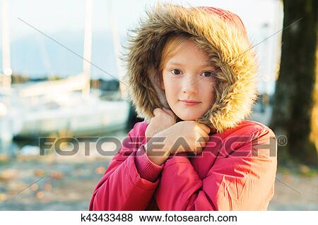 94b479f68 Outdoor close up portrait of cute 9-10 year old little girl wearing warm  winter jacket with hood and fur Stock Photo