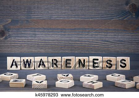 stock photo awareness word written on wood block dark wood background with texture