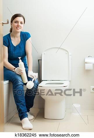 Smiling Woman Cleaning Toilet With Brush And Cleaner At Home