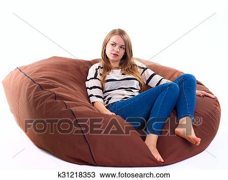 Cute Girl Sitting On A Braun Beanbag Chair.