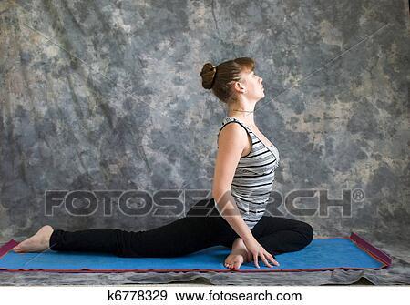 young woman on yoga mat doing yoga posture salamba