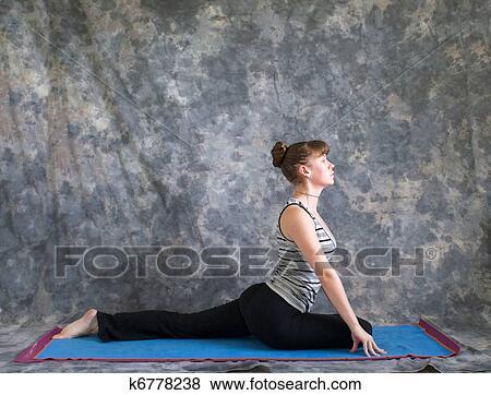 young woman on yoga matdoing yoga posture salamba