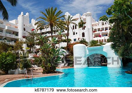 Swimming pool with waterfall and building of luxury hotel, Tenerife island,  Spain Stock Photo