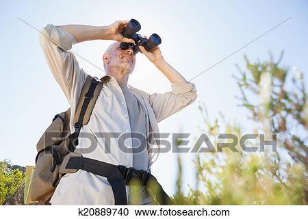 Stock fotografie wanderer stehen auf land spur sehen fernglas
