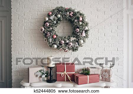 a traditional bright christmas wreath hanging over the fireplace on a white brick wall and packaged gifts are stacked on a fireplace with candles