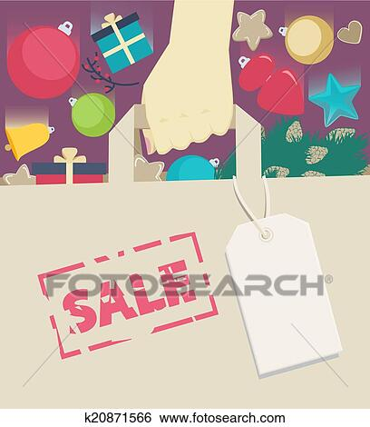 new year sale concept with christmas and new year decorations and gifts falling into a handheld brown paper shopping bag with a blank gift tag or label