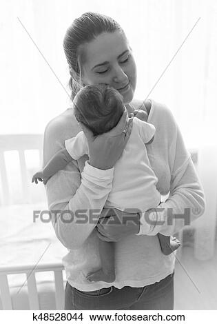 Black And White Portrait Of Beautiful Young Mother Posing With Her Baby Picture K48528044 Fotosearch
