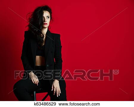 04bec2660 Beautiful sexy woman in black modern stylish jacket and bra underwear red  lipstick rouge on red background looking at the corner