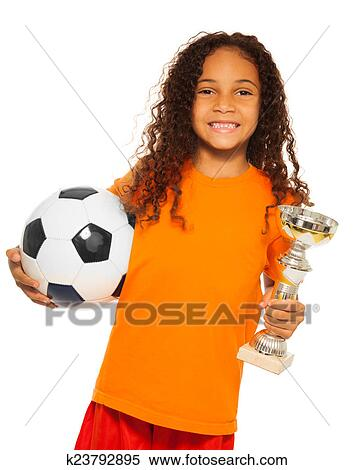 6952445b3 Close portrait of happy African black girl with curly hair holding soccer  ball and winners prize cup wearing sport team uniform standing isolated on  white ...