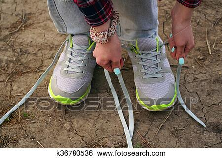 5dba7406bcd85 Stock Image - girl commits an outdoor walk and stopped to tie his shoelaces on  sneakers