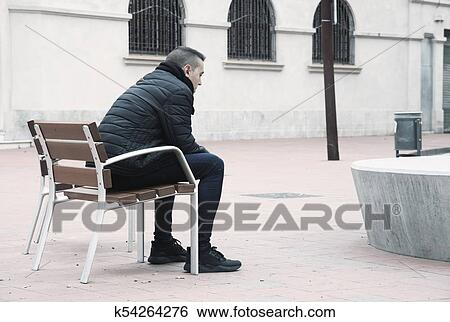 Sad Man Sitting In A Bench In The Street Stock Photograph
