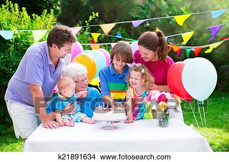 Teenage Boy Toddler Girl And Little Baby Celebrating Birthday Party With Cake Candles In The Garden Decorated Balloons Banners