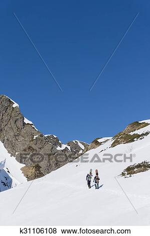 Snowboarders walking uphill for freeride Stock Photo ...