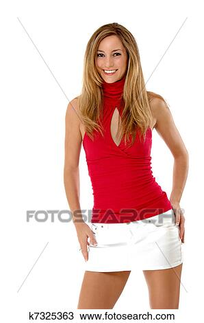 48767b8620aa Three quarter length studio shot of a beautiful young woman isolated on  white. She is smiling and wearing a red shirt and white mini skirt.