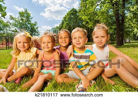 Group Of Hy Little Children Boys And S 3 5 Years Old Sitting On The Gr Lawn In Park Sunny Day Smiling