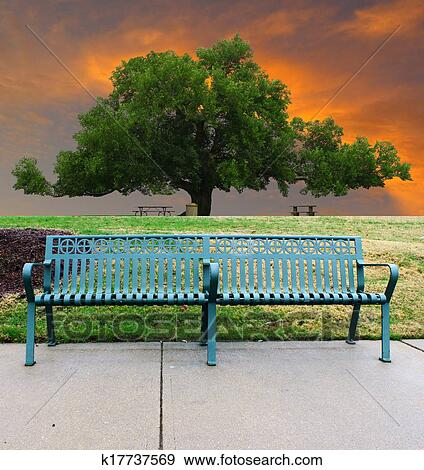 Stock Photograph Of A Lone Single Green Metal Park Bench On The