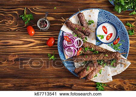 Turkish And Arabic Traditional Ramadan Mix Kebab Plate Kebab Adana Chicken Lamb And Beef On Lavash Bread With Sauce Top View Stock Image K67713541 Fotosearch