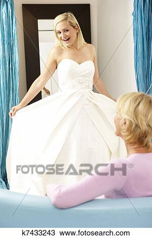 Stock Photo of Bride trying on wedding dress with sales assistant ...