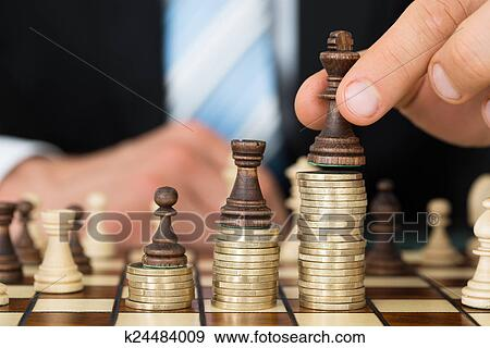 Stock Photograph Of Businessman Placing Chess Pieces On Stacked