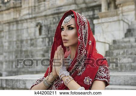 0bc2925607 Beautiful Maharani. Namaste. Indian Woman in Red Bridal Sari clothing with bridal  oriental wedding jewelry. Beautiful Girl in wedding Sari.