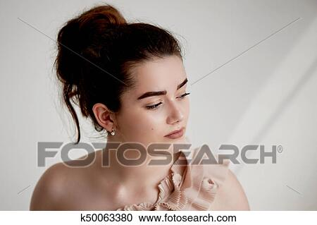1b8646eafbf6 Stock Image - Portrait of young beautiful girl with updo in powdery dress  one shoulder.