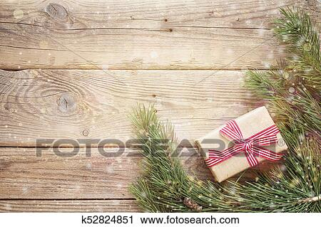 christmas background with gift box and pine branches on an old wooden table holidays background space for text or design top view