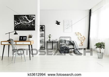 grijze stoel op het bureau met plant en draagbare computer tegen muur met black kaart in tiener slaapkamer met eland boven bed