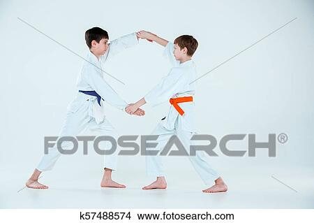 31d08be2d3de3 The teen boys fighting at Aikido training in martial arts school. Healthy  lifestyle and sports concept. Teenagers in white kimono on white background.