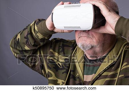 611a842ee8e Senior man in wearable technology VR glasses. Confident old man wearing  camouflage clothing in virtual reality headset with Interface selective  focus hands ...