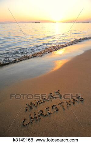 merry christmas handwritten in sand on a beautiful beach - Merry Christmas Beach Images