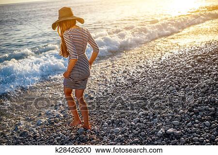 093779d68c Jovem, e, elegante, mulher, em, tirado, vestido, com, um, chapéu, andar,  para, a, mar, praia, ligado, pôr do sol