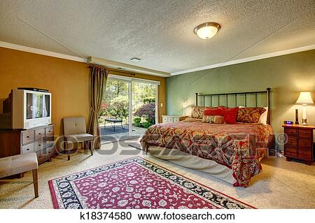 Contrast Color Bedroom With Walkout Deck. Room Furnished With Antique Iron  Frame Bed, Nightstands, Cabinet With Tv And Old Fashioned Chairs.