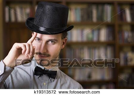 Stock Photo - Attractive young man wearing top hat and bow tie. Fotosearch  - Search bfbe293f8f91