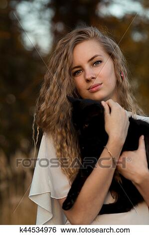 Nice Girl With Her Favourite Pet Black Cat Beautiful Happy Smiling Blonde Girl Hold Black Cat In Hands Cute Girl With Long Curly Hair Hug Little Small Black Cat Cute Friendly