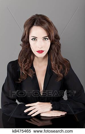 640d544a237 Portrait of a beautiful brunette serious seductress woman in black casual  sitting at table isolated on gray background