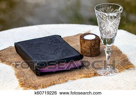Taking Communion  Cup of glass with red wine, bread and Holy Bible on  wooden table close-up Stock Photograph