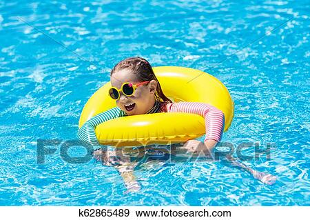 31d93109c1 Child with sunglasses in swimming pool. Little girl on inflatable ring. Kid  with colorful float. Kids learn to swim and dive in outdoor pool of  tropical ...