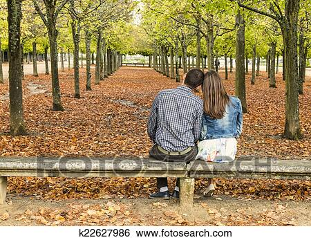 Young Couple Sitting On A Bench In A Park In Autumn Stock Images