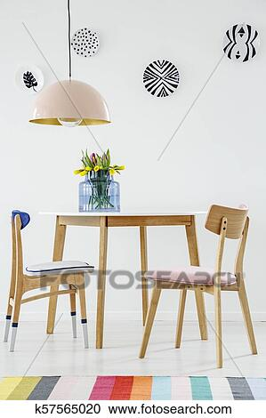 Colorful dining room interior with a table, chairs, striped rug, pastel  chandelier and hanging plates on the wall Stock Image