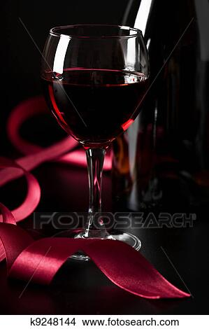 Vetro Vino Rosso E Nastro Rosso Sopra Sfondo Nero Immagine