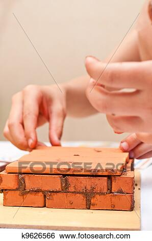 Children Build A Small House Made Of Bricks Stock Photograph