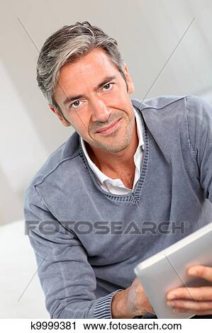 40 Year Old Man At Home Using Electronic Tablet