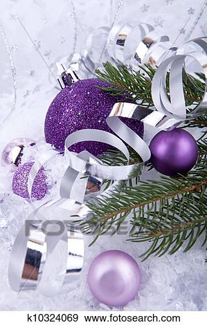 beautiful christmas decoration in purple and silver on white snow sparkle